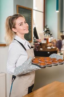 Vista laterale di una giovane donna con vassoio di muffin appena sfornati