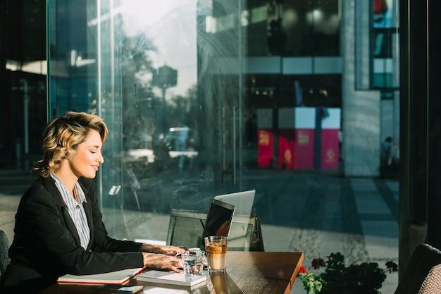 Vista laterale di una giovane donna di affari sorridente che lavora al computer portatile nel ristorante