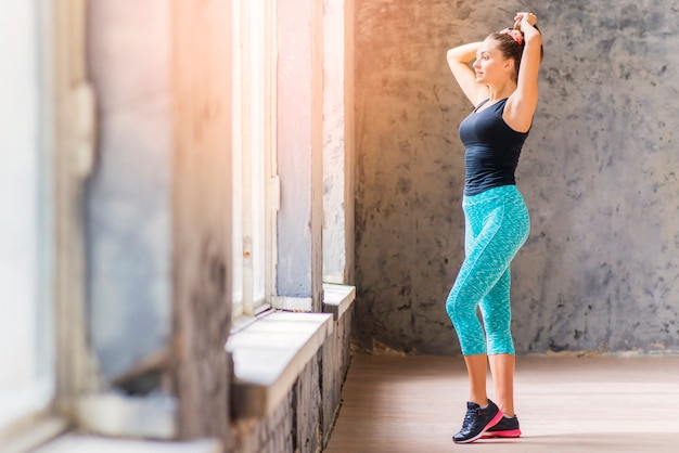 Vista laterale di una giovane donna di forma fisica che sta davanti alla finestra che lega i suoi capelli