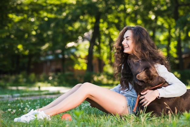 Vista laterale di una giovane donna felice che si siede con il suo cane in giardino