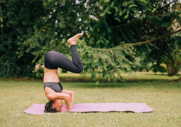 Vista laterale di una giovane donna praticare yoga nel parco