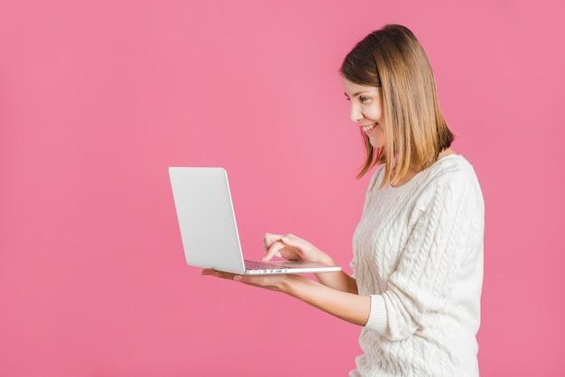 Vista laterale di una giovane donna sorridente che lavora al computer portatile su sfondo rosa