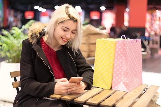 Vista laterale di una giovane donna sorridente seduto sul bar