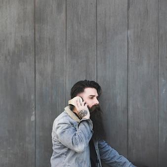 Vista laterale di una musica d'ascolto del giovane sulla cuffia contro la parete di legno grigia