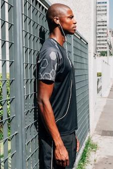Vista laterale di una musica d'ascolto di giovane atleta maschio africano su auricolari in piedi vicino al cancello