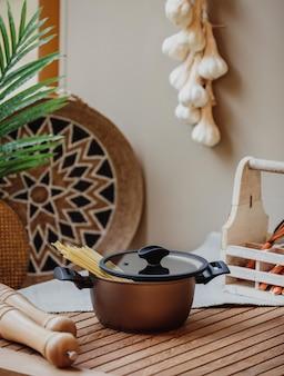 Vista laterale di una padella con spaghetti crudi su un tavolo di legno