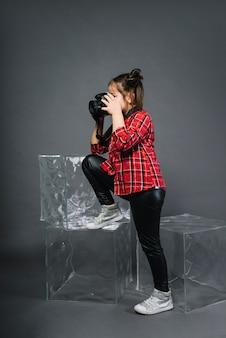 Vista laterale di una ragazza che fotografa con la macchina fotografica che sta vicino ai blocchi