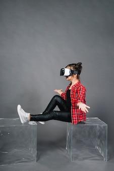 Vista laterale di una ragazza che indossa occhiali di realtà virtuale scrollando le spalle