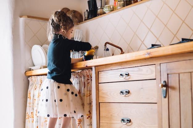 Vista laterale di una ragazza che lava tazza in cucina