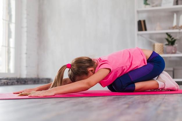 Vista laterale di una ragazza che si esercita sulla stuoia di esercizio rosa a casa