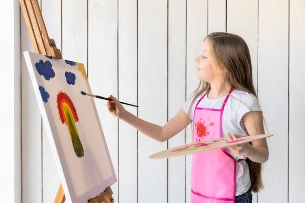 Vista laterale di una ragazza che tiene la pittura disponibile della tavolozza di legno sul cavalletto con il pennello