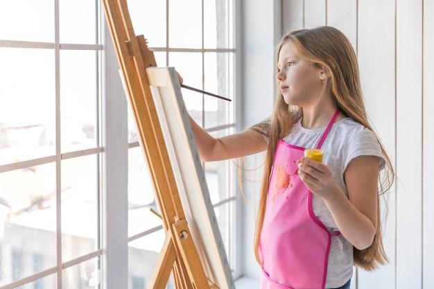 Vista laterale di una ragazza che tiene la pittura gialla della bottiglia disponibile della pittura sul cavalletto con il pennello