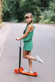 Vista laterale di una ragazza in piedi su una gamba sopra lo scooter sulla strada