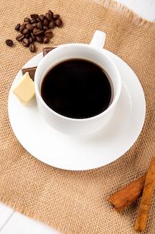 Vista laterale di una tazza di caffè con bastoncini di cannella e chicchi di caffè sparsi su fondo rustico