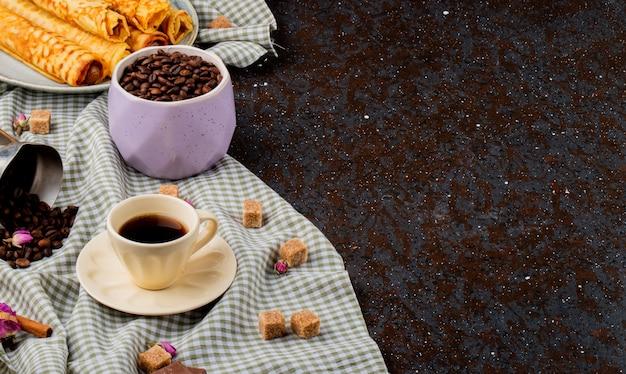 Vista laterale di una tazza di caffè e zucchero di canna cubetti di cioccolato e chicchi di caffè sparsi sulla tovaglia plaid con spazio di copia