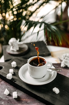 Vista laterale di una tazza di caffè su un tagliere di legno