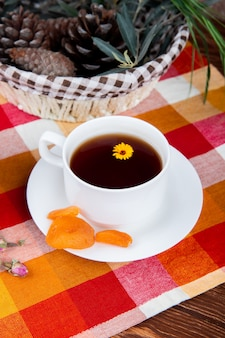 Vista laterale di una tazza di tè con albicocche secche e pigne in un cestino sulla tovaglia plaid