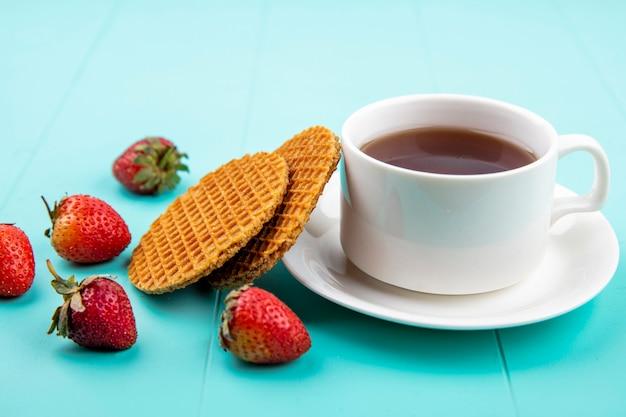 Vista laterale di una tazza di tè con cialde e fragole sulla superficie blu