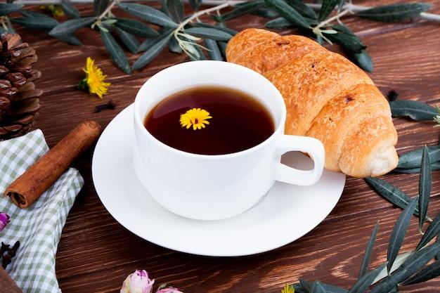 Vista laterale di una tazza di tè con cornetto e denti di leone su legno