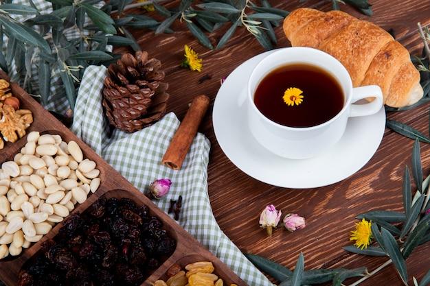 Vista laterale di una tazza di tè con cornetto, noci miste con frutta secca e denti di leone sparsi su legno