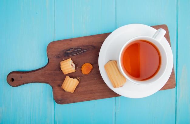 Vista laterale di una tazza di tè con i biscotti e l'albicocca secca sul tagliere di legno sul blu