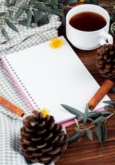 Vista laterale di uno sketchbook con una tazza di tè e denti di leone sparsi e pigne su legno