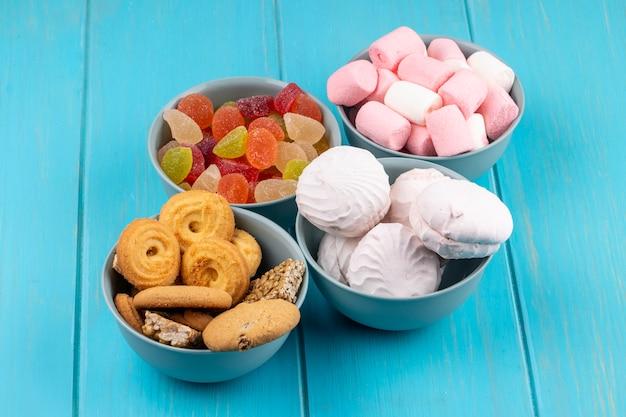 Vista laterale di vari dolci in ciotole come biscotti bianco zefiro e caramelle gommosa e molle con caramelle colorate marmellata d'arance sul blu