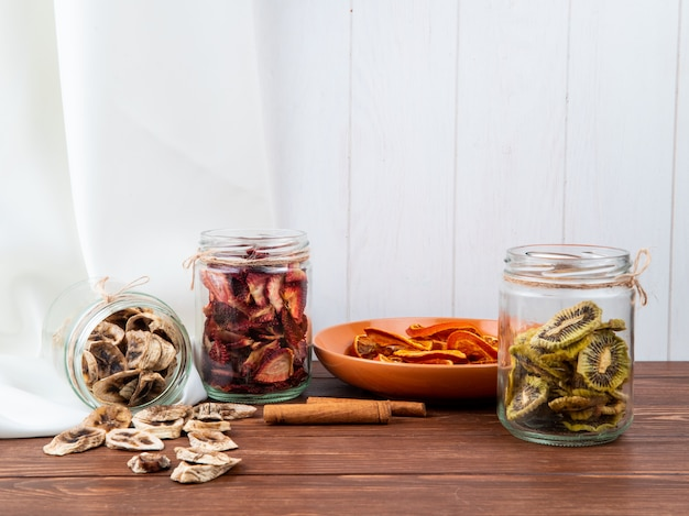 Vista laterale di vari frutti affettati secchi in barattoli di vetro banana kiwi e fragola su fondo di legno