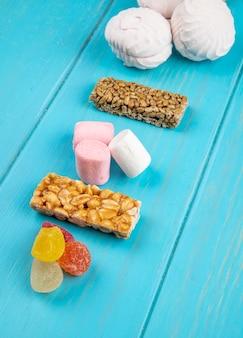 Vista laterale di varie barre del miele dei dolci delle caramelle marshmallow e della marmellata d'arance delle noci e dei semi sull'azzurro