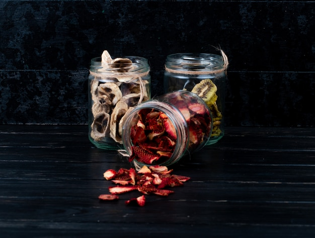 Vista laterale di varie fette di frutta secca in barattoli di vetro fragola banana e kiwi su sfondo nero