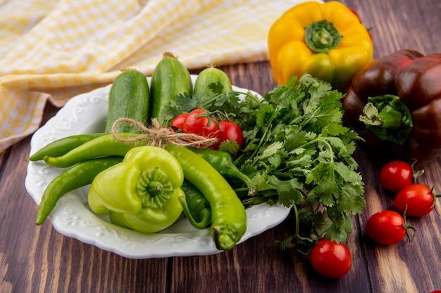 Vista laterale di verdure come cetriolo pepe coriandolo in piastra e panno plaid con pomodori su legno