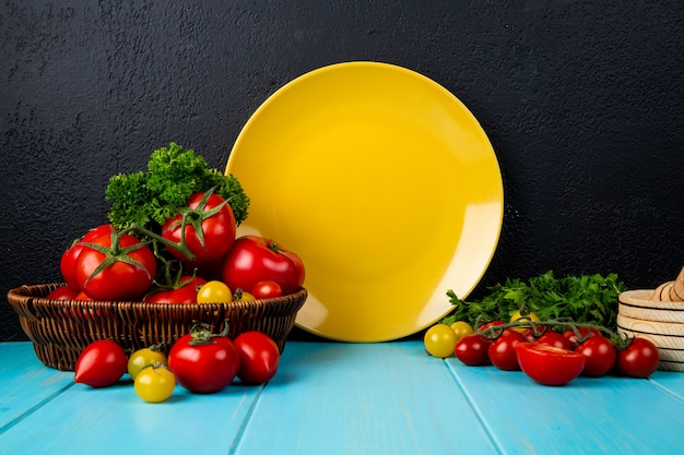 Vista laterale di verdure come coriandolo e pomodoro nel cestino con altri e frantoio di aglio con piatto vuoto sulla superficie blu e sfondo nero