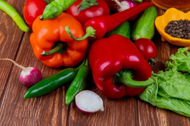 Vista laterale di verdure fresche colorate peperoni cetrioli pomodori maturi peperoncini verdi ravanello e grani di pepe neri su legno rustico