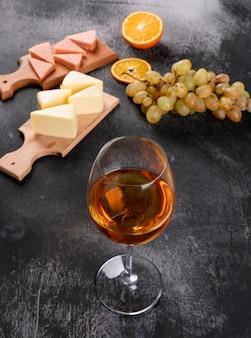 Vista laterale di vino bianco con l'uva, l'arancia ed il formaggio sul tagliere di legno sul verticale di superficie di buio