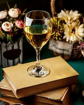 Vista laterale di vino bianco in vetro sul libro
