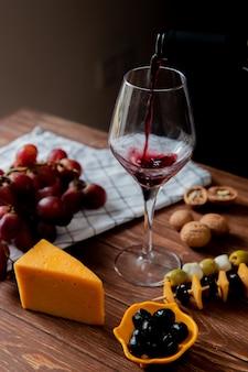 Vista laterale di vino rosso che versa nel vetro con l'uva della noce di oliva verde oliva del parmigiano e del cheddar su superficie di legno e su fondo nero