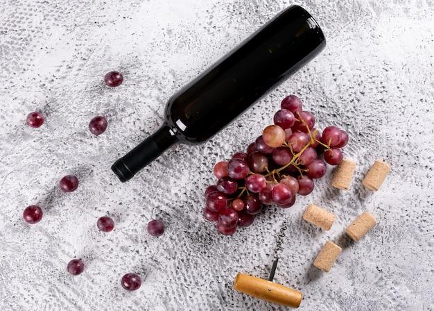 Vista laterale di vino rosso con l'uva sull'orizzontale di pietra bianco