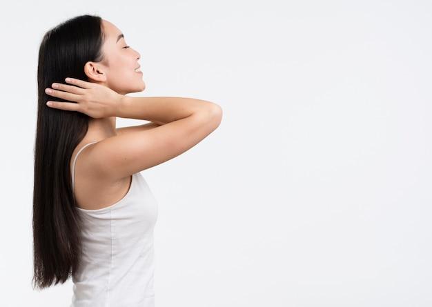 Vista laterale donna che si prende cura dei suoi capelli
