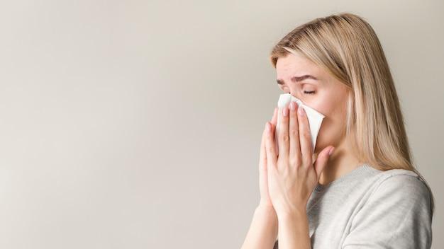 Vista laterale donna che soffia il naso