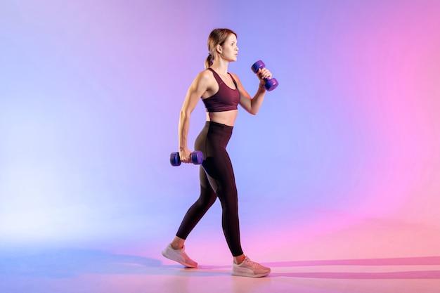Vista laterale donna con pesi