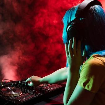 Vista laterale femmina dj sul pannello di controllo