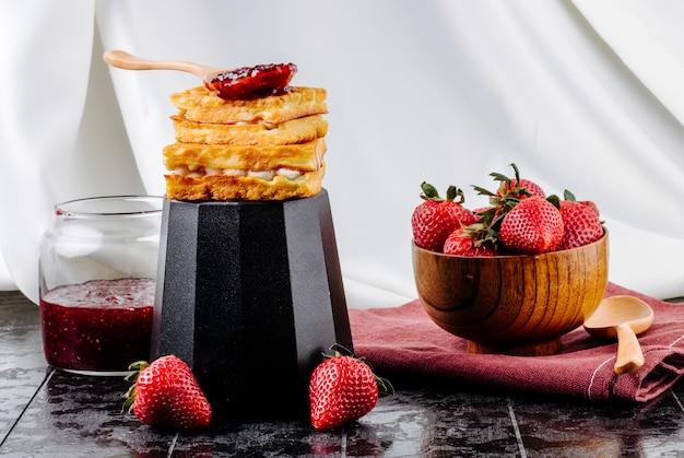 Vista laterale fragola e cialde con crema alla vaniglia e marmellata di fragole in cima