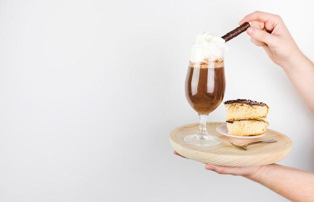 Vista laterale frappe e torta su un piatto di legno