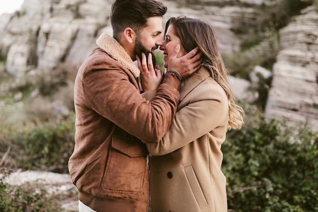 Vista laterale giovane coppia a baciarsi in natura