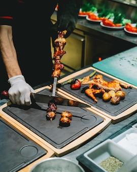 Vista laterale il cuoco rimuove da uno spiedino tike kebab su una tavola con pollo alla griglia e verdure