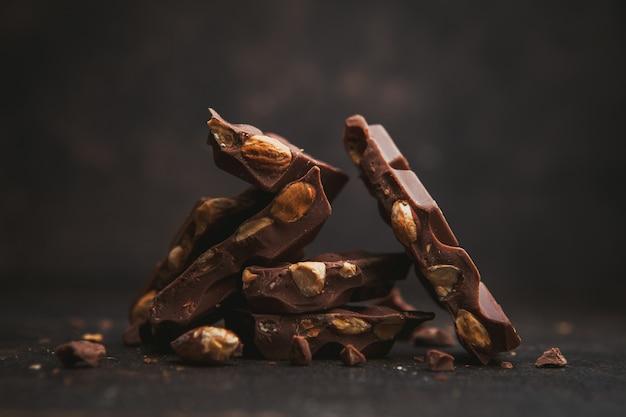 Vista laterale mandorla con cioccolato su marrone scuro.