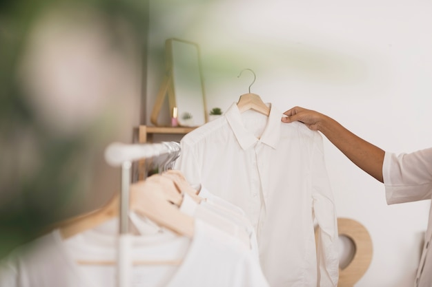 Vista laterale mano scegliendo una camicia bianca