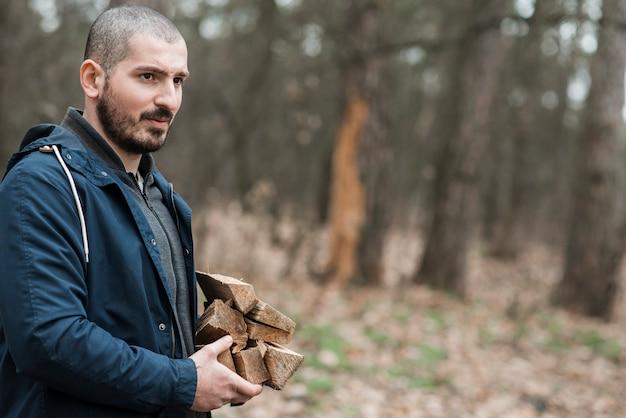 Vista laterale maschio che trasporta legno