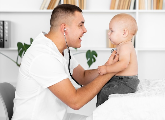 Vista laterale medico ascolto piccolo bambino con stetoscopio