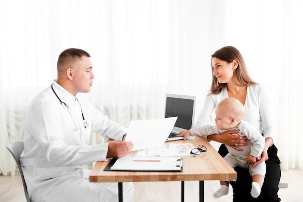 Vista laterale medico consulenza bambino appena nato